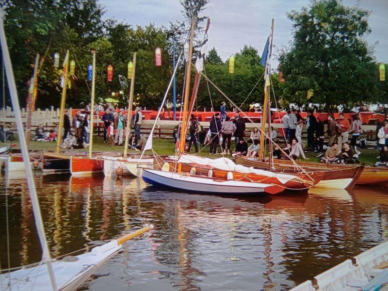 Plusieurs bateaux rangés dans le port ; le public au loin