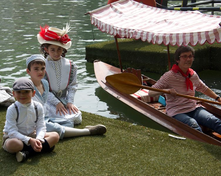 3 petits enfants costumés sont assis par terre sur le quai à côté de la périssoire