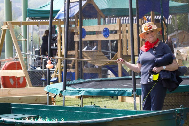 Une dame avec un canotier montre un canard en plastique au bout d'une canne à pêche